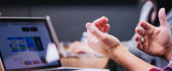 Man's hands open in front of computer screen